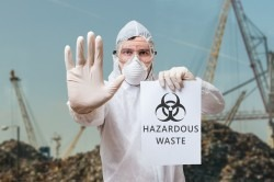 Technician in overall warns in landfill about hazardous waste.